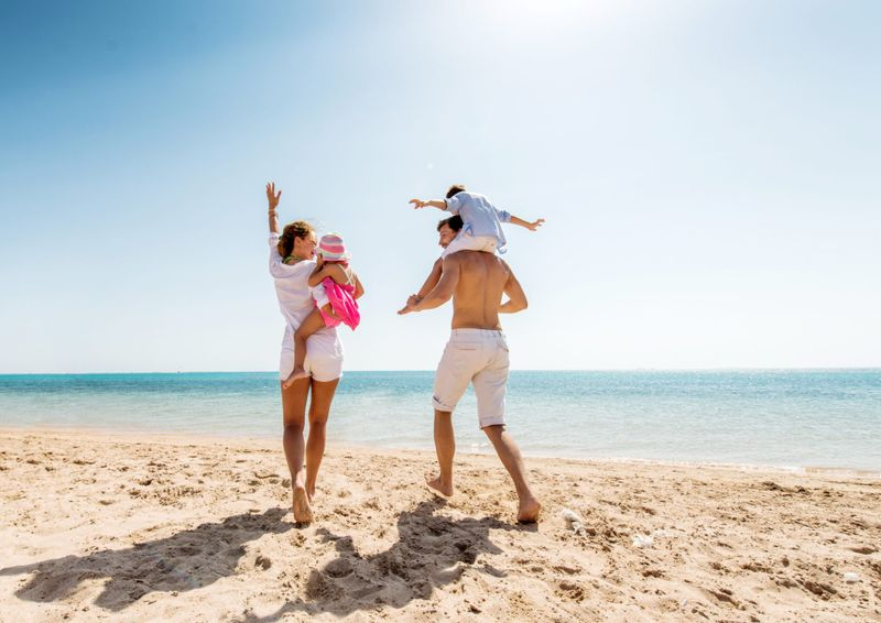 Cheerful parents enjoying at the beach with their little children.