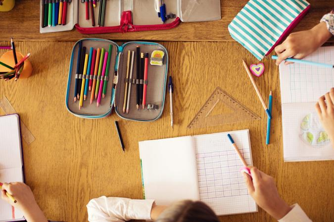 Pupils in school working and drawing in their notebooks.