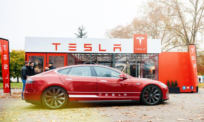 Paris: View from the street of new Tesla Model S showroom parked in front of the showroom with customers admiring the red electric luxury car.