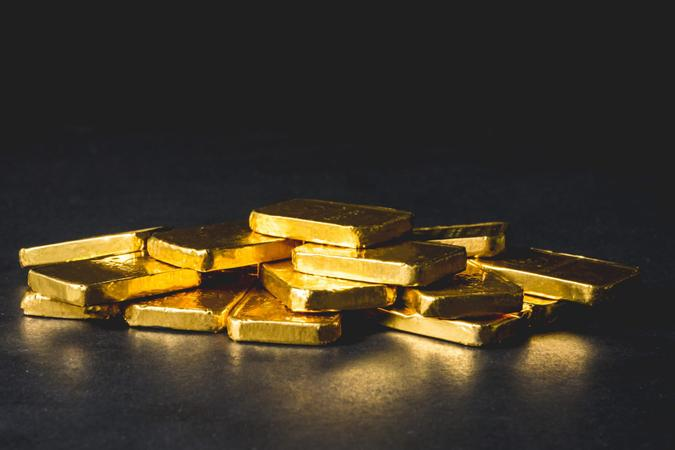 Stack of Pure gold bars on black background.