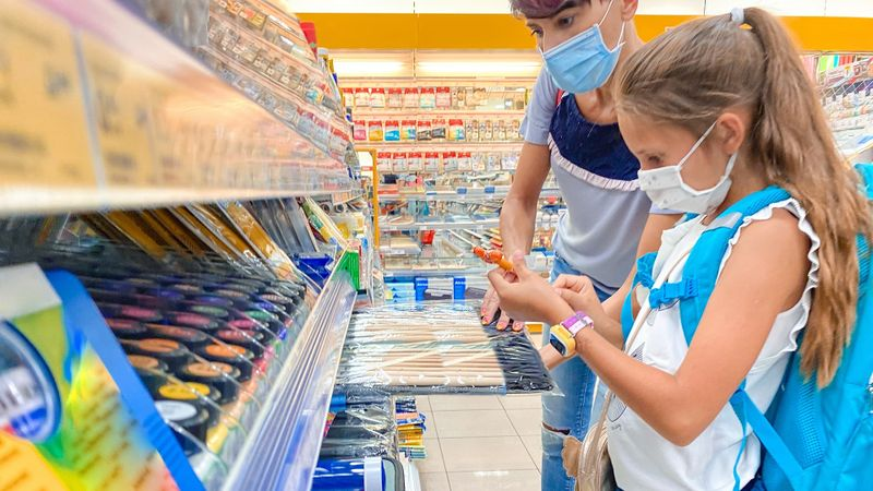 Adult Woman Browsing Trough School Supplies in Store with her Daughter Preparing for New School Year During Pandemic - stock photo stock photo