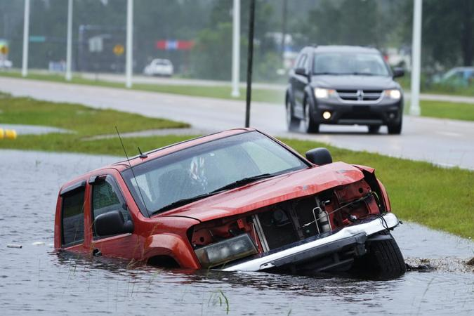 Mandatory Credit: Photo by Steve Helber/AP/Shutterstock (12382734a)An abandoned vehicle is half submerged in a ditch next to a near flooded highway as the outer bands of Hurricane Ida arrive, in Bay Saint Louis, MissTropical Weather Atlantic, Bay Saint Louis, United States - 29 Aug 2021.