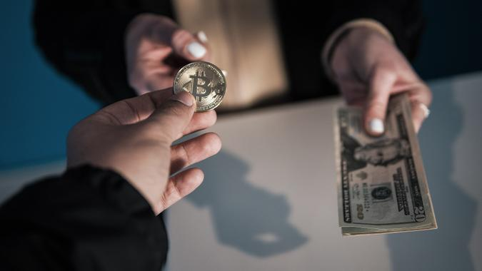 Exchanging Bitcoin with United States Dollar Bill stock photo