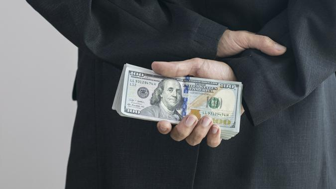 Corruption concept by business man is hide the money at back. stock photo