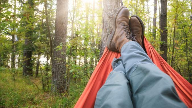 Person wearing trekking pants and hiking boots relaxing laying in camping hammock overlooking summer forest at sunset.