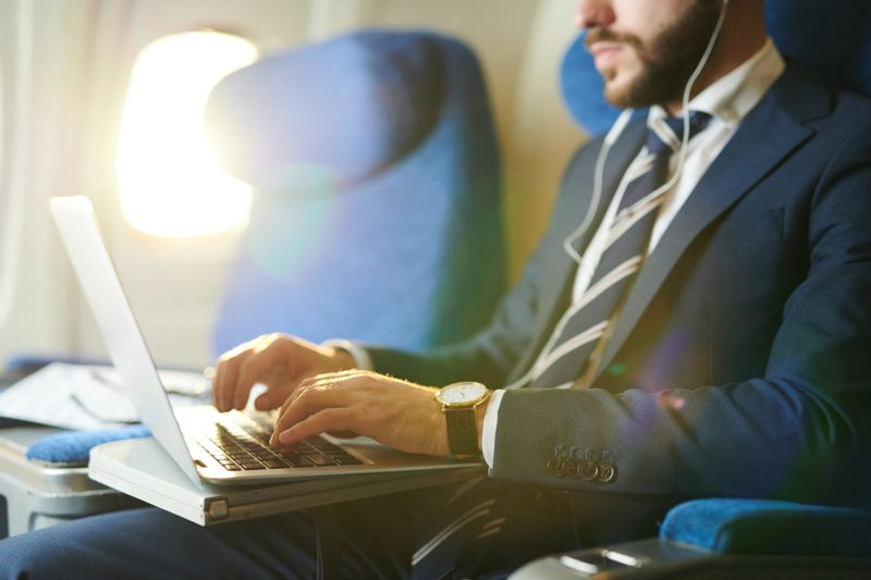 Mid section portrait of unrecognizable businessman typing on keyboard while using laptop during first class flight in plane, copy space.