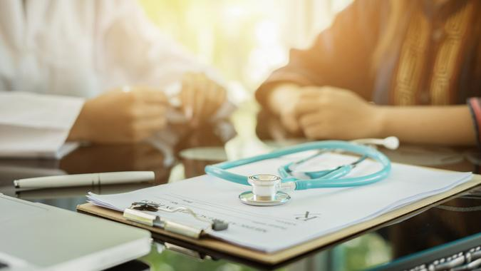 Stethoscope with clipboard and Laptop on desk,Doctor working in hospital writing a prescription, Healthcare and medical concept,test results in background,vintage color,selective focus.