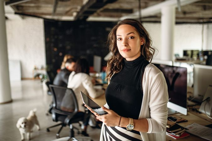 Portrait of a young business woman in the modern office, and a team behind her.