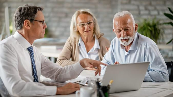 Senior couple using laptop with their financial advisor during a meeting int he office.