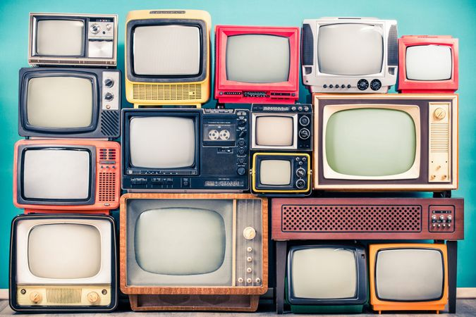 Retro TV receivers set from circa 60s, 70s and 80s of XX century, old wooden television stand with amplifier front mint blue wall background.