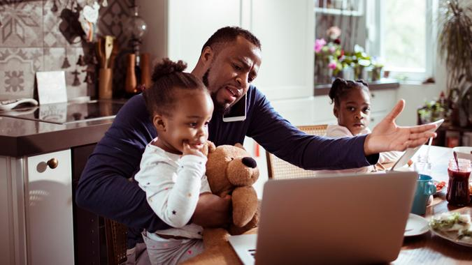 Close up of a young family using a laptop in the morning , while the father is talking on the phone.