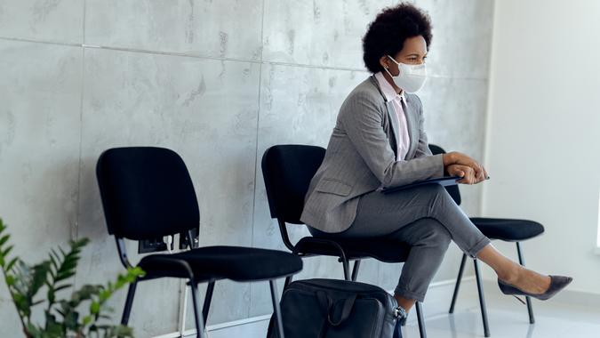 Distraught African American businesswoman wearing protective face mask while sitting in a hallway and waiting for job interview.