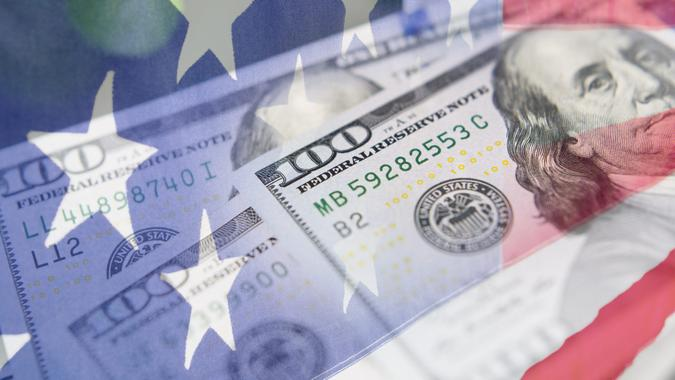 Composite design of the American Flag and cash money to depict the Stimulus checks Americans received during the COVID-19 crisis.