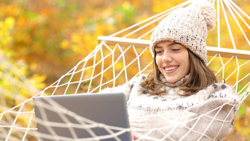 Happy woman on hammock using laptop in autumn.