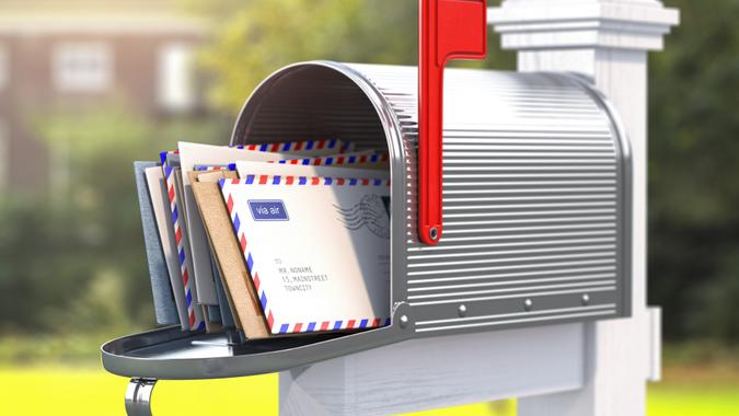 Open mailbox with letters on rural backgound.