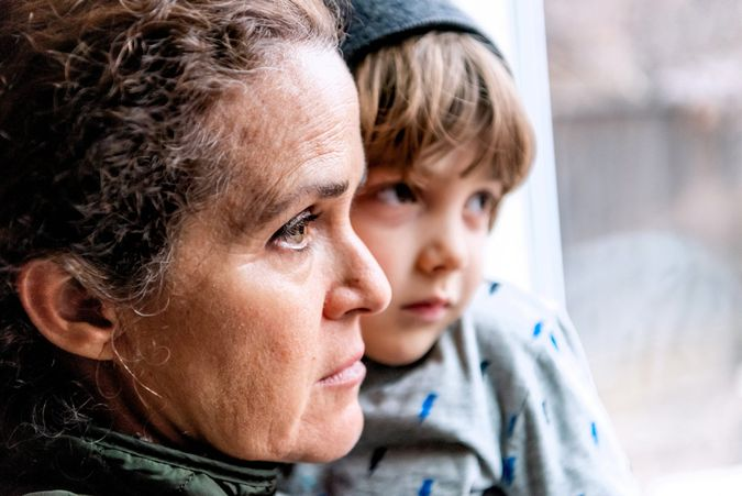 Caucasian Mature woman posing with her son, very sad looking through window worried about loss of her job due Covid-19 pandemic.