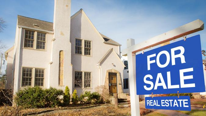 A classic Tudor style house in the mid-west of United States for sale with sale sign on lawn.