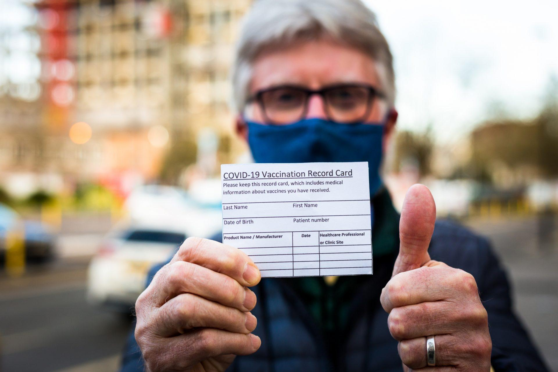 Close up color image depicting a senior man in his 70s holding a card outdoors in the city with details of his covid-19 vaccination.