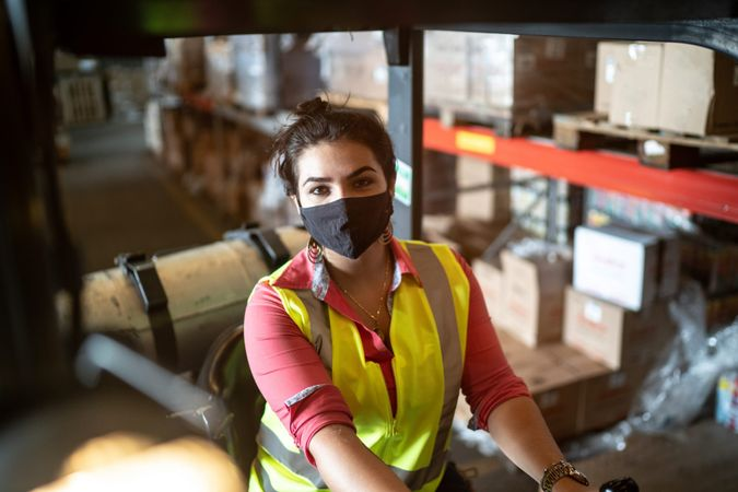 Portrait of a young woman using face mask driving a forklift in a warehouse.