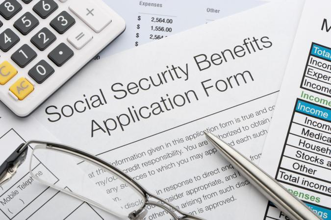 Close up of social security application with calculator and pen.