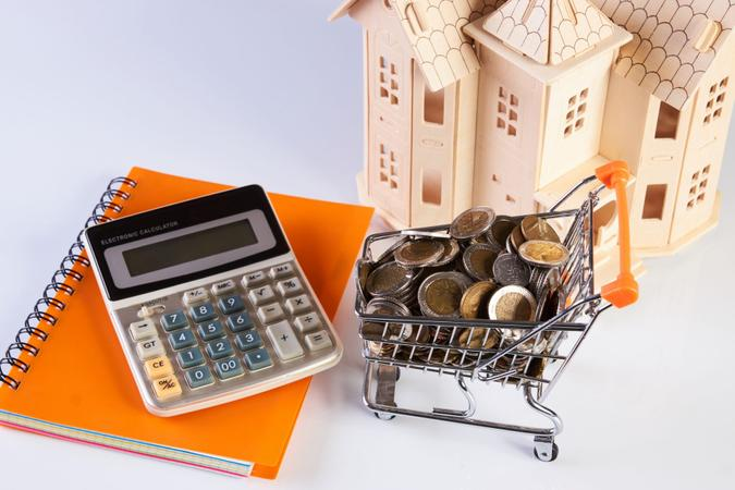Wood house model, coins in shopping cart and financial notebook on desk table.