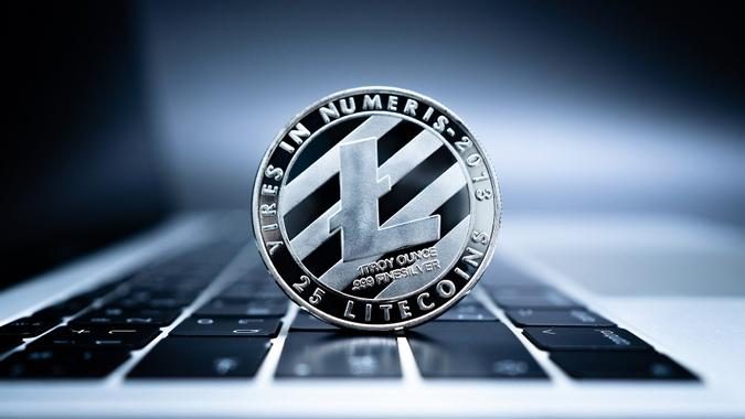Close up of silver coin Litecoin on laptop computer keyboard. stock photo
