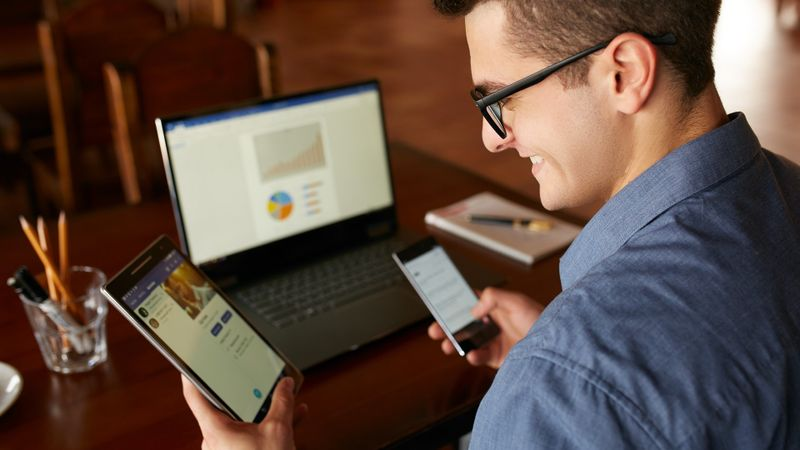 Attractive man in glasses working with multiple electronic internet devices. Freelancer businessman has laptop and smartphone in hands and laptop on table with charts on screen. Multitasking theme stock photo