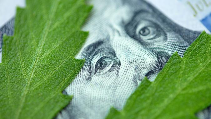 American dollar bill on cannabis leaves. Concept taxation and marijuana, tax on weed, money and pot. Cannabis finance. Revenues the marijuana industry and medical industry. Economy of hemp industry stock photo