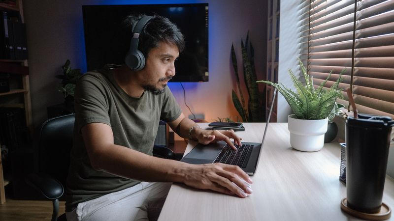 Millennial man playing computer game on laptop at home. stock photo