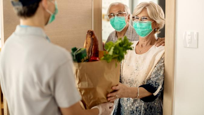 Happy mature woman and her husband receiving groceries at home during coronavirus epidemic. stock photo