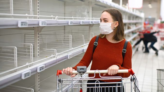 Young woman standing in front of empty shelf in a supermarket stock photo