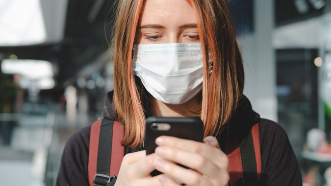 Woman in protective face mask using the phone at a public place. stock photo