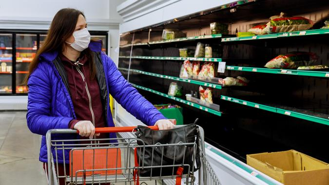 Woman with protection face mask and gloves shopping at supermarket. stock photo