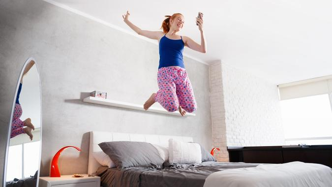 Good News For Happy Young Woman Girl Jumping On Bed stock photo