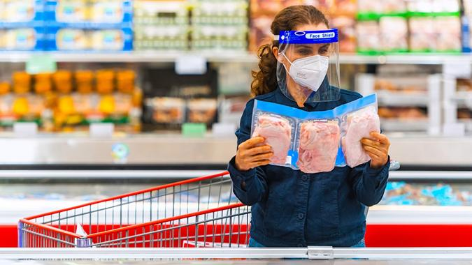 Mature woman shopping for frozen chicken at a supermarket stock photo
