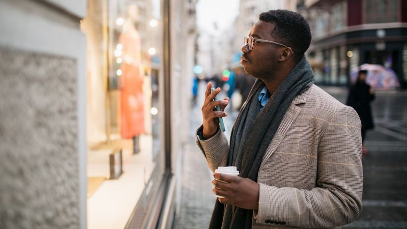 Side view of a young African American man in front of a store window stock photo