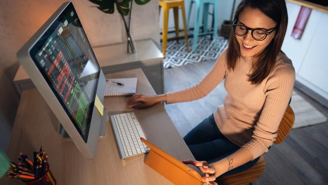 High-angle view of a young woman trading cryptocurrency on a computer and digital tablet stock photo