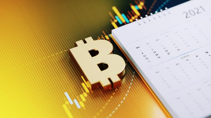 Investment And Financial Planning Concept - Bitcoin Symbol Sitting Next To The White 2021 Calendar On Yellow Financial Graph Background stock photo
