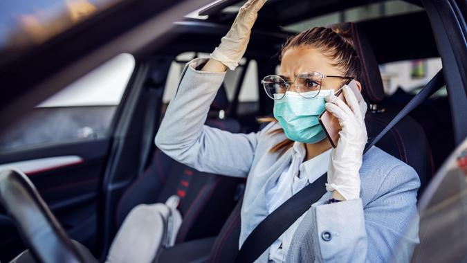 Businesswoman with protective mask and gloves on sitting in her car caught in traffic jam sitting in her car and having phone conversation. She is very nervous. Protection form corona virus concept. stock photo