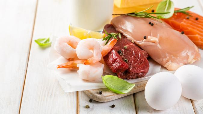 Selection of aminal protein sources - beef, chicken, salmon, cheese, milk, eggs, shrimps on wood background.
