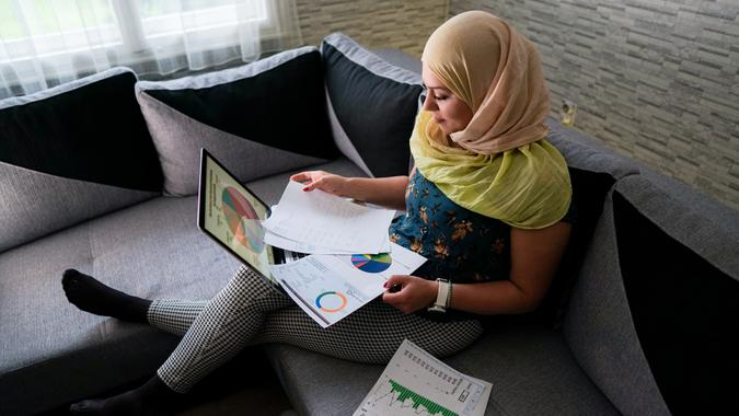 Islamic business woman investing online from home.