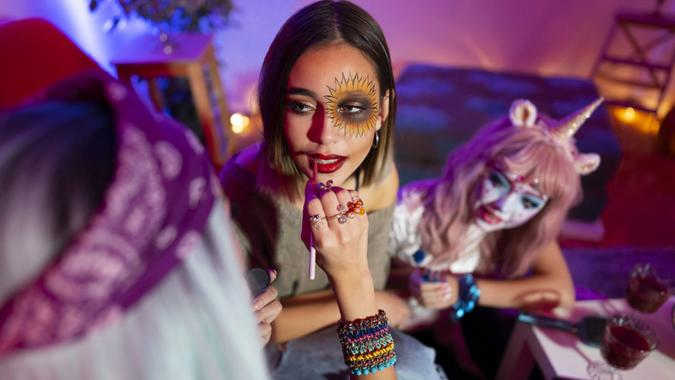 Girls preparing for Halloween party, doing make-up at home before going out.