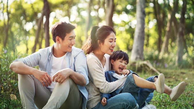 young asian parents and son having fun outdoors in park.