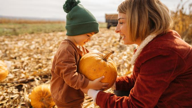 Photo of a young mother and her son collecting pumpkins on a pumpkin patch; family on a Halloween pumpkin patch adventure.
