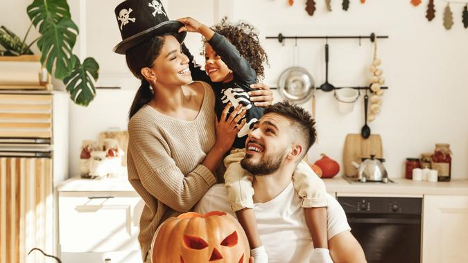 happy multiethnic family mother, father and little son have fun and celebrate Halloween at home.