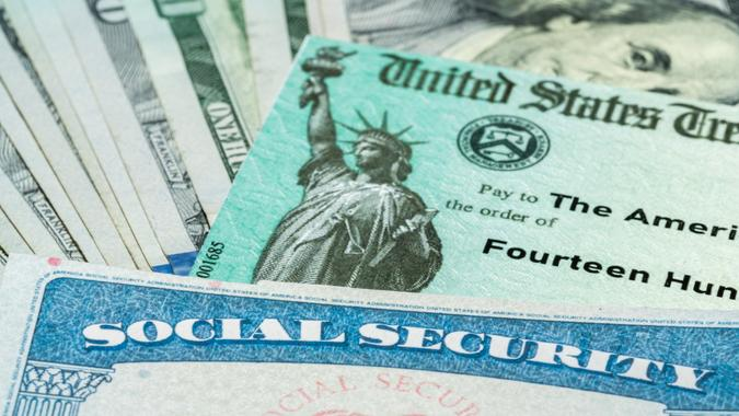 Stack of 100 dollar bills with US Treasury illustrative check to illustrate American Rescue Plan Act of 2021 payment with social security card for retirees.