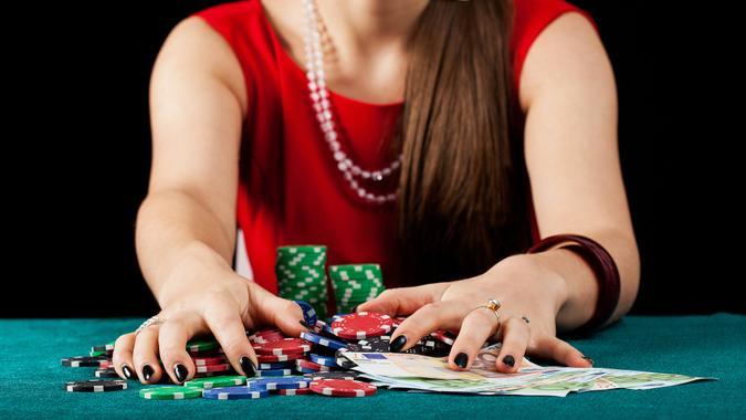 An elegant female gambler taking chips and banknotes.