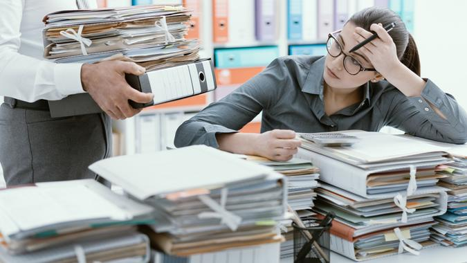 Young stressed secretary in the office overwhelmed by work and desk full of files, her boss is bringing more paperwork to her.