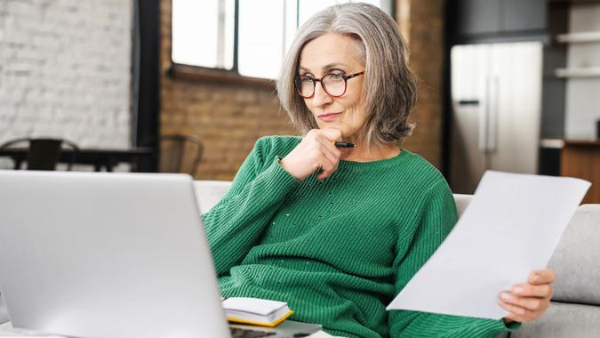 Serious senior accountant sitting on the living room and looking at the laptop stock photo