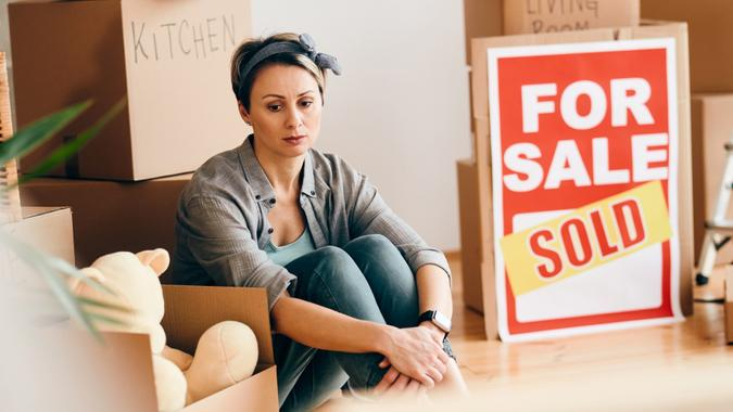 Sad woman sitting among her belongings after selling her home. stock photo